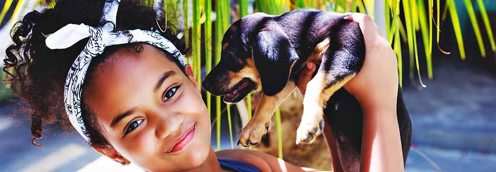 Fille métisse avec cheveux bouclés accompagnée de son chien